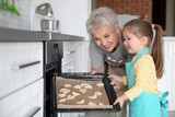 Cute little girl and her grandmother making cookies on kitchen - 192037628