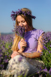 Charming girl in a hat and a light dress posing in a lavender field at sunset - 192037690