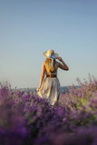 Charming girl in a hat and a light dress in a lavender field in a hat - 192037831