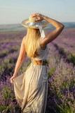 Charming girl in a hat and a light dress in a lavender field in a hat - 192037834