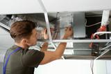 Male technician repairing industrial air conditioner indoors - 192038817