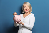Happy mature woman putting coin into piggy bank on color background - 192038851