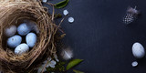 Happy Easter;  Easter eggs in nest and spring flower on table background - 192039245