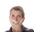 Man hiding his true emotions by covering his mouth with a fake smile drawn on his hand.
