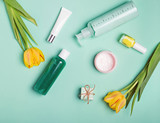 Bottles with feminine body care producs and yellow tulips on the bright background - 192046445