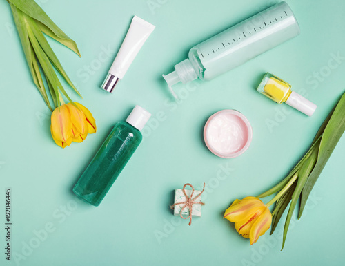 Bottles with feminine body care producs and yellow tulips on the bright background