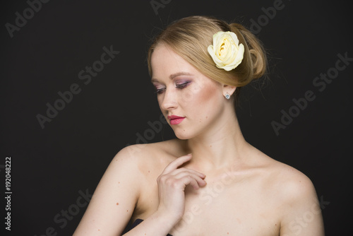 Fotobehang Kiev blonde with a yellow rose in her hair posing on a gray background