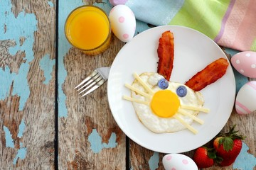 Easter breakfast with cute bunny face made of egg and bacon. Table scene, above view over a rustic blue wood background.