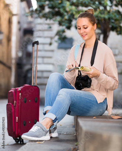 Tourist woman is sitting down on curb
