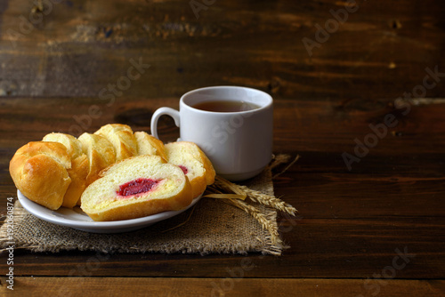 homemade cakes - pastries with cream cheese and strawberry jam and a white Cup of tea on dark wooden background