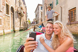 Couple taking selfie in Venice Gondola romantic boat ride happy tourists on honeymoon travel vacation holidays. Young people sailing in Venetian canal in gondola. Italy. Europe holiday. - 192062038
