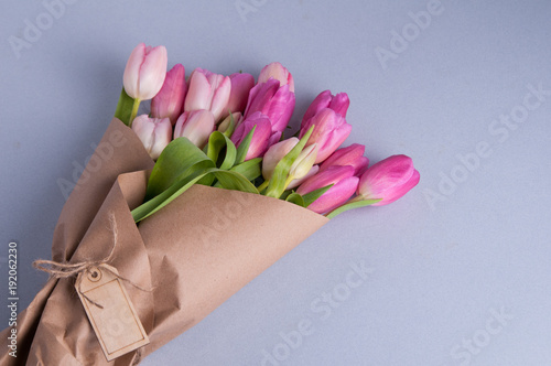 pink spring tulips wrapped in brown paper on a blue background