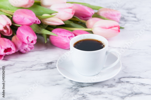 Plagát cup of coffee and pink tulips on a marble counter top