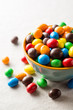 Quadro Colorful chocolate buttons in bowl on gray stone background.