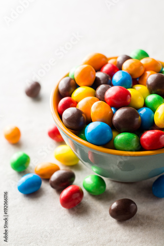 Colorful chocolate buttons in bowl on gray stone background.