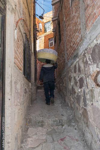 Papiers peints Ruelle etroite From the back, a man with a basket of laundry on his head, walking up a narrow stone pathway, between two stone walls, in Guanajuato, Mexico
