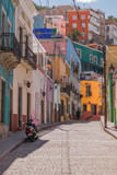 A hilly cobblestone street with many colorful houses and one scooter, parked, in Guanajuato, Mexico - 192074638