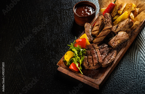 Papiers peints Steakhouse Assorted delicious grilled meat with vegetable. Mixed grilled bbq meat with vegetables. Mixed grilled meat on wooden platter