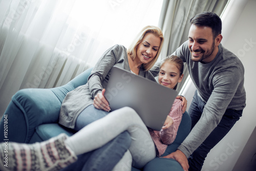 Lovely family watching a movie on laptop at home