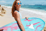 Female tourist spends spare time and summer holidays in tropical hot country, wears sunglasses and bathing suit, holds surf board, stands at beach against ocean. Healthy lifestyle and rest concept - 192082260