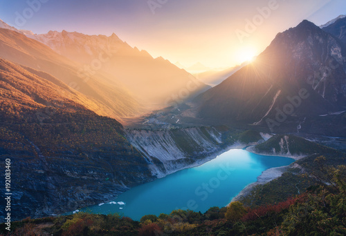 Mountains and lake with blue water at sunset in Nepal. Majestic landscape with high mountains, lake, lightened hills, rocks, yellow sunlight and blue sky. Bright sunny evening. Travel. Nature © den-belitsky