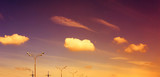Street lamps and high-power pylons on sunset sky with clouds background. - 192087291