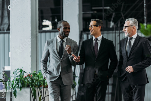Wall mural smiling multiracial businessmen having conversation while walking in office