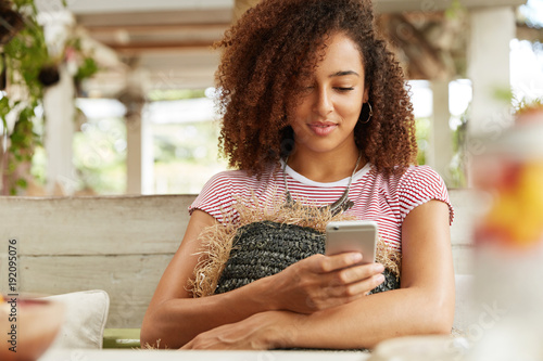 Image of African American female with curly hairstyle rests at cafe on couch huggs cushion, checks own email and messages with friends in social networks, uses mobile phone and wireless internet