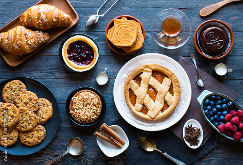 Top view of a wood table full of cakes, fruits, coffee, biscuits, spices and more - 192099032