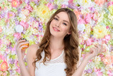 beautiful young woman spraying perfume on floral background - 192099227