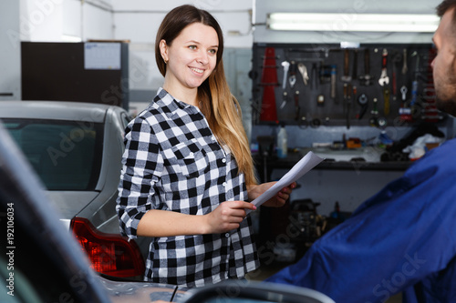 Smiling female is satisfied of tire replacement of her car in spring