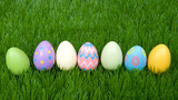 Colorful decorative and plain easter eggs lined up in a row in green grass. - 192112444