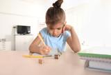 Cute little girl doing homework indoors - 192115036
