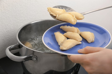 Woman putting cooked dumplings on plate, closeup