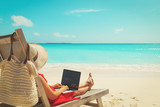remote work concept -young woman with laptop on beach - 192120026