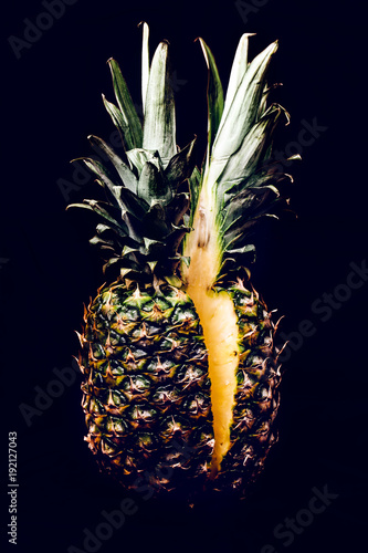 cuted in half pineapple on black background, creative photo