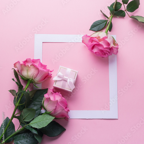 Fresh pink roses and gift with a frame on a pink background. Flat layout. Copy space. Minimalism. Celebratory concept. Selective focus
