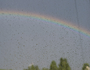 A rainbow behind a wet window