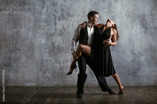 Fototapeta Young pretty woman in black dress and man dance tango