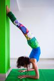 woman practice handstand against wall yoga class indoor - 192134016