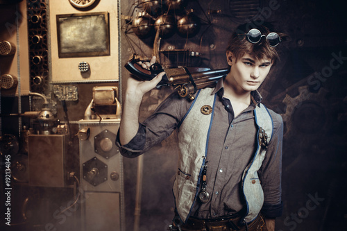 Portrait of a young steampunk man wearing weapons and mechanical goggles.