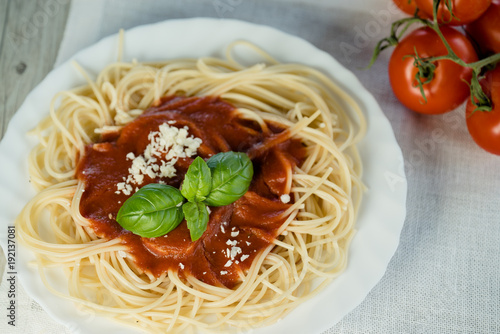 Italian pasta spaghetti topped with a tomato and fresh basil - 192137081