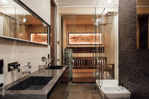 Wnętrze łazienki jest w brązowych kolorach z bidetem, dwoma umywalkami, szklanym prysznicem i sauną za szklanymi drzwiami