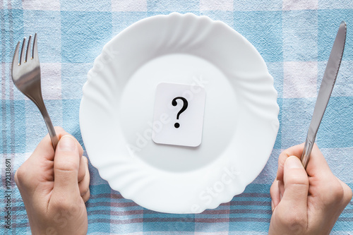 Woman's hands holding a fork and knife. Question mark in the clean, empty, white plate on the tablecloth. Starving people. Meal waiting concept. Top view. - 192138691