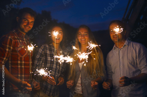 Young happpy people with sparklers having fun