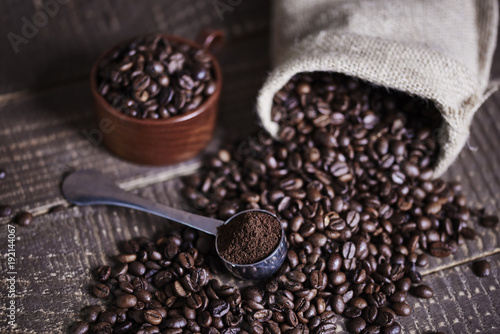 Beans of coffee and jute bag on wooden table