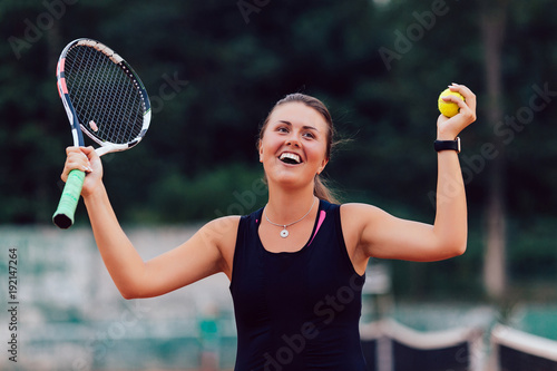 Fotobehang Tennis Tennis player. Glad beautiful woman showing happy emotion after winning tennis match, raising racket and ball. Outdoors.