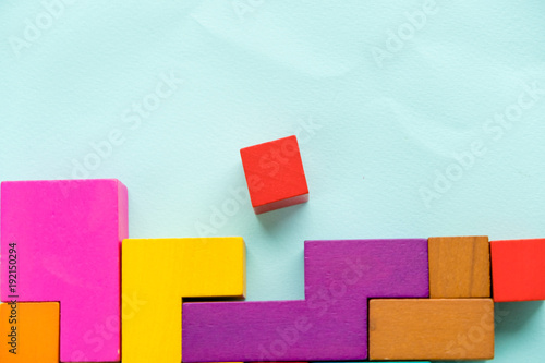 Different colorful shapes wooden blocks on blue background, flat lay. Geometric shapes in different colors, top view. Concept of creative, logical thinking or problem solving. Copy space. © yavdat