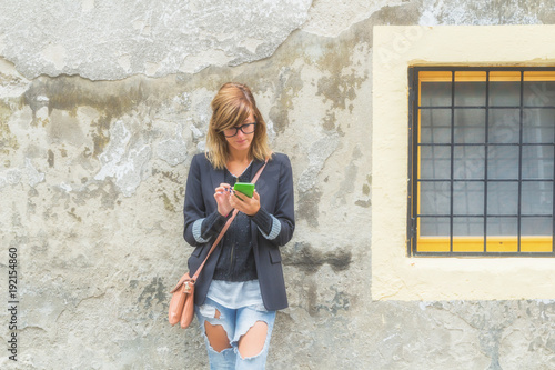 Cute woman holding cellphone in urban surroundings.