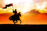 Medieval knight on horse carrying a flag - 192158641